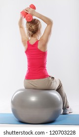 Woman sitting on a ball and doing exercise with dumbbells view from the back