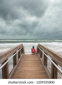 Woman sitting on beach boardwalk watching hurricane come in from the Gulf of Mexico.