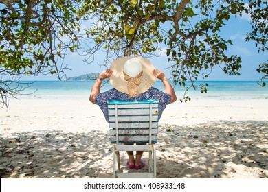 Woman sitting on a beach chair under a tree enjoying a summer day at the beach. Concept on the beach