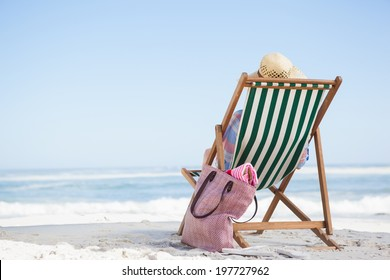 Woman sitting on beach in deck chair on a sunny day