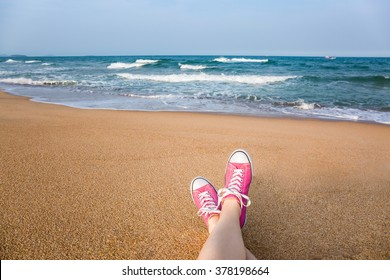 Woman sitting on the beach with first person perspective view, legs in focus