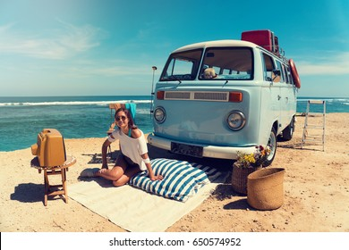 Woman is sitting on the beach for a picnic near a vintage car, next to an old TV set. Summer holidays, road trip, vacation, travel and people concept - smiling young women next a vintage minivan car