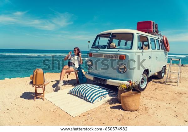 Frau sitzt am Strand, um ein Picknick in der Nähe eines Vintage-Autos, neben einem alten Fernseher. Sommerferien, Straßenfahrt, Urlaub, Reise und Menschen Konzept - Lächelnde junge Frauen neben einem Vintage-Miniwagen