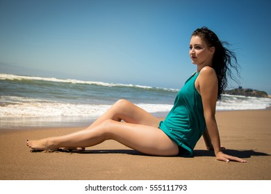 Woman sitting on beach sunbathing wearing blue top and black bikini. Blue eyes and dark hair. Beautiful blue skies and sandy beach.