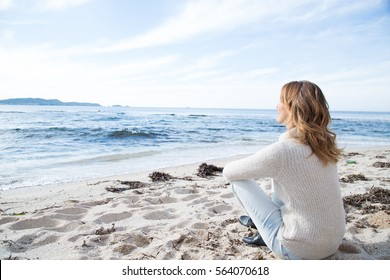 woman sitting on the beach in winter