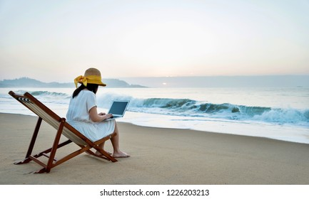 Woman sitting on beach and working with laptop.