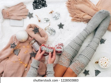 Woman sitting on bed with Christmas decorations , cozy flat lay, holiday lazy