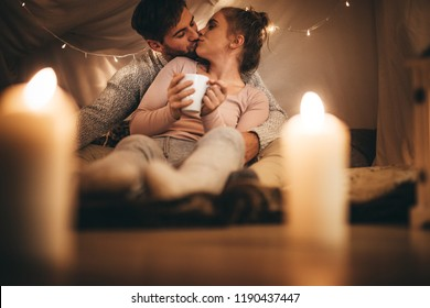 Woman sitting on bed with her husband holding a coffee cup and kissing him. Couple in love kissing while sitting on bed in room lit with candles and tiny light bulbs.