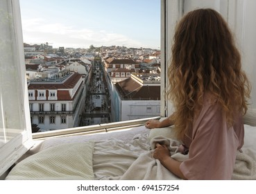 Woman sitting on the bed in the hotel room and looking at view from window at Lisbon city streets