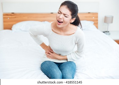 Woman sitting on the bed and touching her left side in pain at home