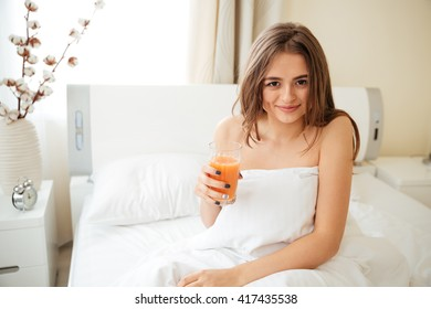 Woman sitting on the bed under blanket and drinking juice at home