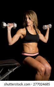 a woman sitting on a bench, doing shoulder presses.  Working her muscles.