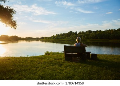 Woman Sitting On Bench During A Beautiful Sunset