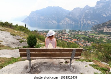 Woman sitting on bench in front of panorama of Lake Garda and mountains, Italy