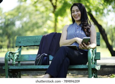 The woman sitting on the bench and happy face and smiling with mobile phone on hand in the green park. Happy beautiful long-haired girl spending her free time in a summer  texting on the mobile phone
