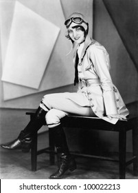 Woman sitting on a bench in a pilots uniform