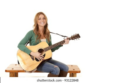 A woman sitting on a bench playing her guitar.