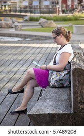 Woman sitting on a bench reading in Western Harbour, Malmoe