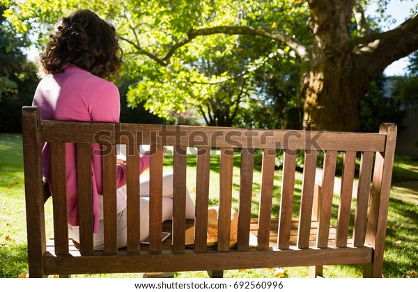 Woman sitting on bench and reading book at the garden