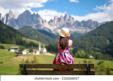 Woman sitting on bench relaxing her holiday travel to Dolomites in Italy. she wearing pink dress and straw hat with flower Looking to beautiful mountain peaks and the church of Santa Maddalena
