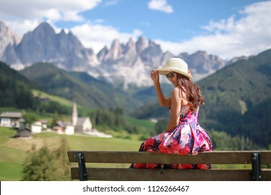 Woman sitting on bench relaxing her holiday travel to Dolomites in Italy. she wearing pink dress and straw hat with flower