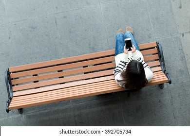 Woman sitting on bench and use of mobile phone