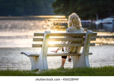 Woman sitting on a bench watching the sun set at the beach at Swartswood Lake State Park in New Jersey