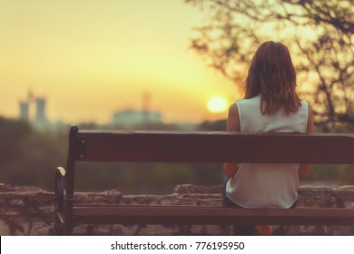 Woman sitting on a bench and watching the distant city scenery.