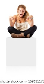 Woman sitting on blank empty box, pointing down at copy space.