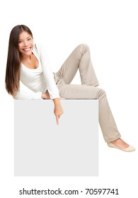 Woman sitting on blank empty paper poster, pointing down at copy space. Whole body image of cute casual woman in white isolated on white background.