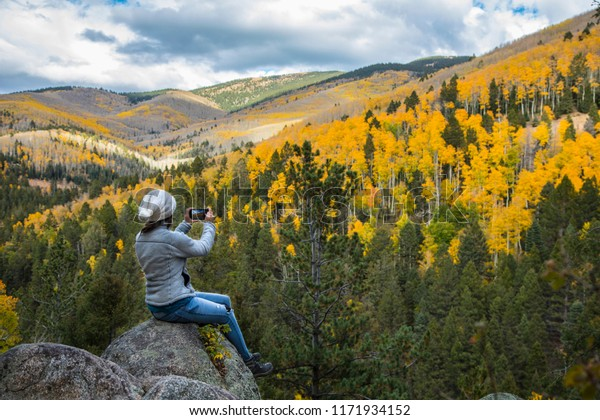 Woman sitting on a boulder taking a picture of the fall foliage with her phone