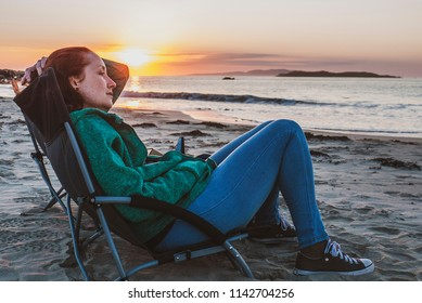 Woman sitting on a camping chair on a sandy beach watching a beautiful sunset over a calm ocean. Taken on Renvyle Beach along the Wild Atlantic Way in Ireland in summer.