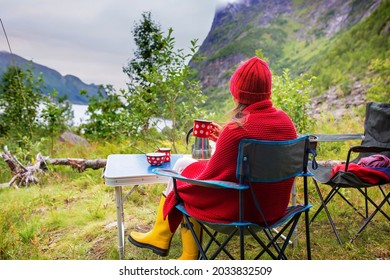 Woman, sitting on a camping chair in front of a tent, enjoying cup of coffee and amazing view in Norway Nordland, Senja island in the morning, wild camping. Woman with blanket, hat and rainboots