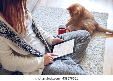 Woman sitting on the carpet near the sofa using a tablet with headphones,drinking coffee from a red cup. Next to it lies a thick red cat.  Online education concept. e-learning. . Pet shop concept