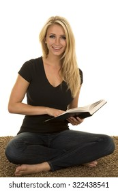 A woman sitting on the carpet reading a book with a smile on her face.