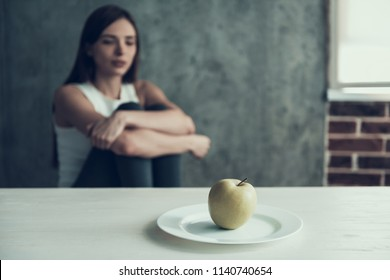 Woman Sitting on Chair and Eating One Apple. Diet Concept. Weight Loss Problem. Starving Young Woman. One Apple on White Plate. Hungry Woman. Healthy Lifestyle Concept. Starving Vegetarian.