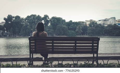 Woman sitting on a chair in front of a lake alone in loneliness concept.