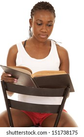 A woman sitting on a chair reading a book with a serious expression