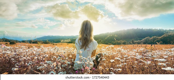 Woman sitting on the chamomiles field and looking at the cloudy sky at sunset. Banner edition.