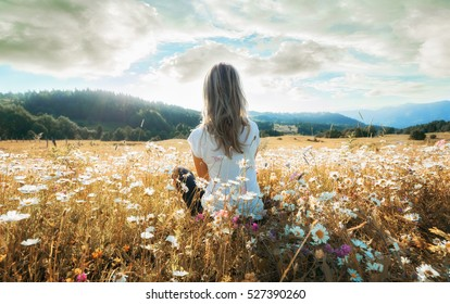 Woman sitting on the chamomiles field and looking at the mountain and sun.