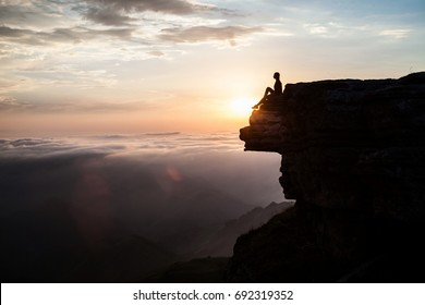 Woman sitting on the cliff and enjoying sunset