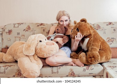 Woman sitting on couch with her plush toys