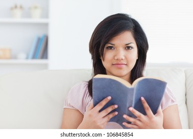 Woman sitting on a couch and holding a book in a living room