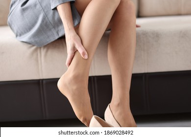Woman is sitting on couch and holding on to sore leg closeup. Varicose veins of lower leg concept