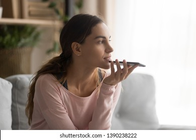 Woman sitting on couch holds phone talks on speakerphone with friend, makes voice recognition or request uses internet services through virtual assistant, record audio message, translator app concept