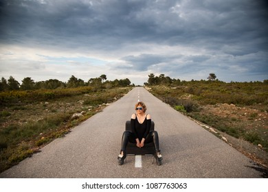 Woman sitting on a couch in the middle of a road
