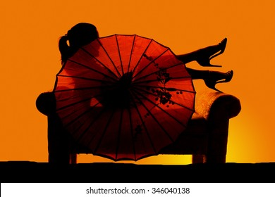A woman sitting on a couch with the sheer umbrella.