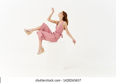 woman sitting on a cube on a white background