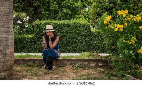 Woman sitting on curb at the beach in white fedora and sarong looking at phone surrounded by flowers and bushes in Khao Lommuak Thailand