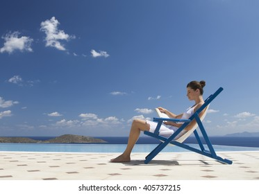 A woman sitting on a deck chair reading a book